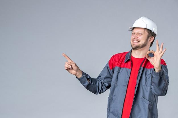 Vista frontal del constructor masculino en uniforme y casco sobre fondo gris