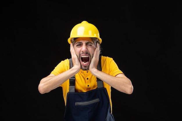 Vista frontal del constructor masculino en uniforme gritando de dolor en la pared negra