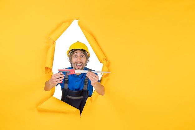 Vista frontal del constructor masculino en uniforme con el instrumento en sus manos en el color del trabajador del constructor del trabajo de la pared amarilla