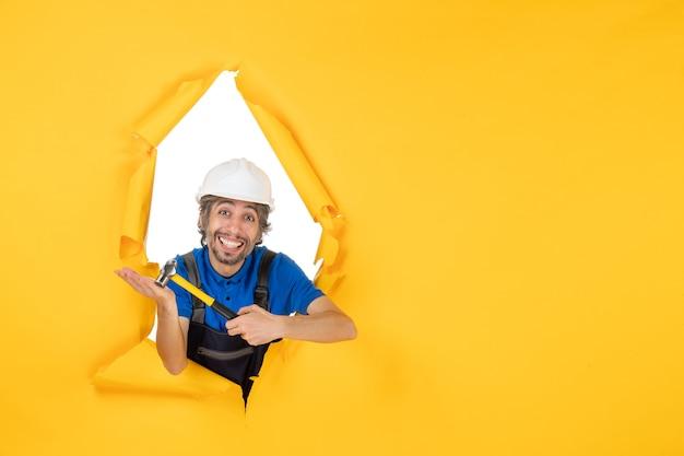 Vista frontal del constructor masculino en uniforme con un martillo en la pared amarilla color trabajador constructor de trabajo hombre de construcción