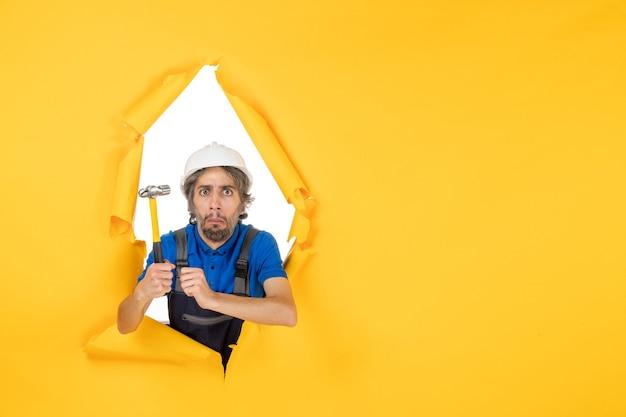 Vista frontal del constructor masculino en uniforme con un martillo en la pared amarilla trabajador hombre construcción trabajo constructor arquitectura color