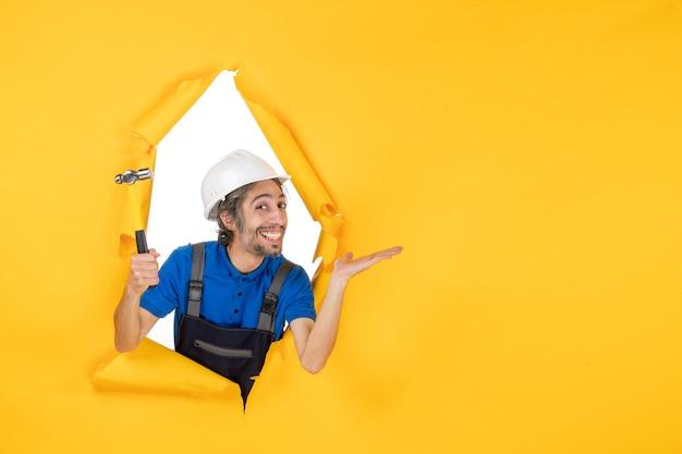 Vista frontal del constructor masculino en uniforme con un martillo en la pared amarilla trabajador hombre constructor arquitectura color trabajo de construcción