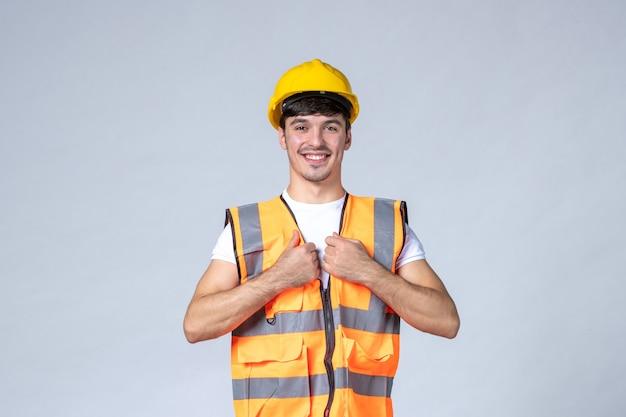 Vista frontal del constructor masculino en uniforme en la pared blanca