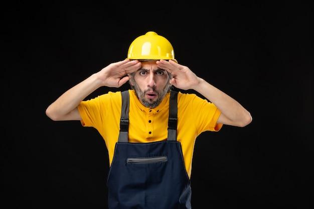 Vista frontal del constructor masculino en uniforme en la pared negra