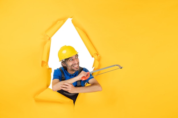 Vista frontal del constructor masculino en uniforme sosteniendo la sierra de arco sobre fondo amarillo