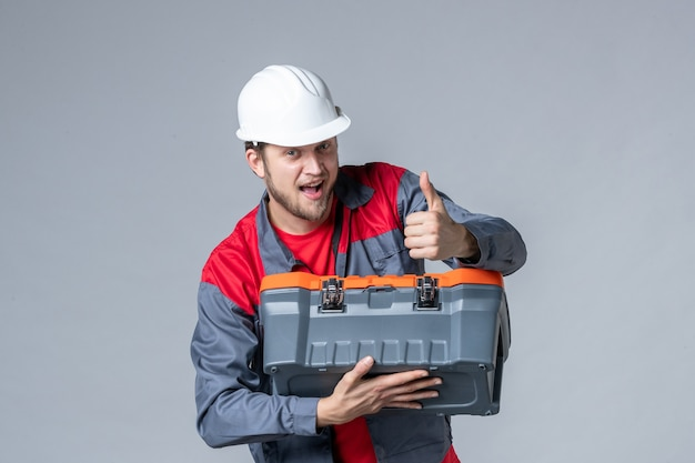 Vista frontal del constructor masculino en uniforme tratando de abrir la caja de herramientas sobre fondo gris