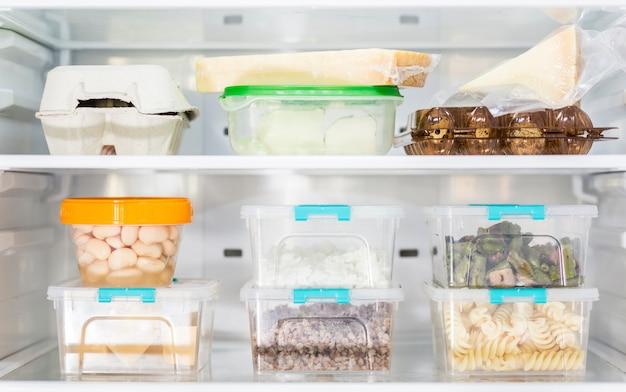 Vista frontal de contenedores organizados de plástico para alimentos en nevera