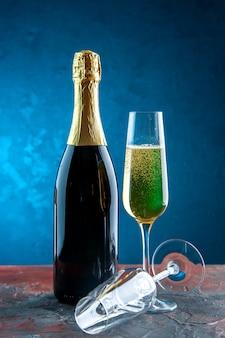 Vista frontal copa de champán con botella en azul celebración fiesta beber alcohol foto color año nuevo