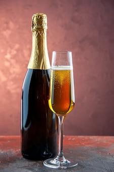 Vista frontal de una copa de champán con una botella de bebida ligera de alcohol color champán año nuevo