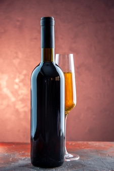 Vista frontal de una copa de champán con una botella en la fiesta de celebración ligera beber alcohol foto color año nuevo