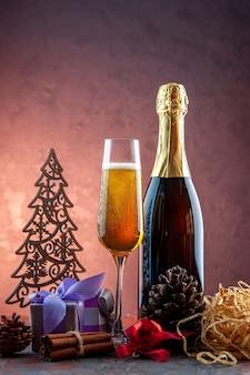 Vista frontal de una copa de champán con regalos y una botella de bebida ligera de alcohol foto color champán año nuevo