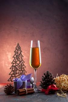 Vista frontal de una copa de champán con regalos y juguetes en una bebida ligera, alcohol, color, champán, año nuevo