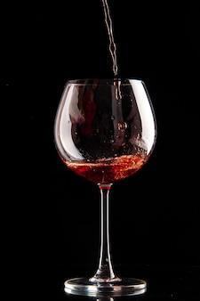 Vista frontal de la copa de vino que se vierte con vino tinto en alcohol de champán de bebida de color negro
