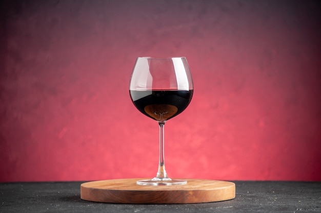 Vista frontal de la copa de vino tinto sobre tablero de madera sobre fondo rojo.