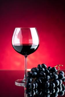 Vista frontal de una copa de vino con uvas en una pared rosada