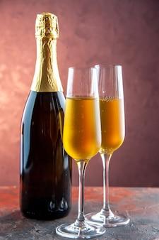 Vista frontal de copas de champán con botella en bebida ligera alcohol foto color champán año nuevo