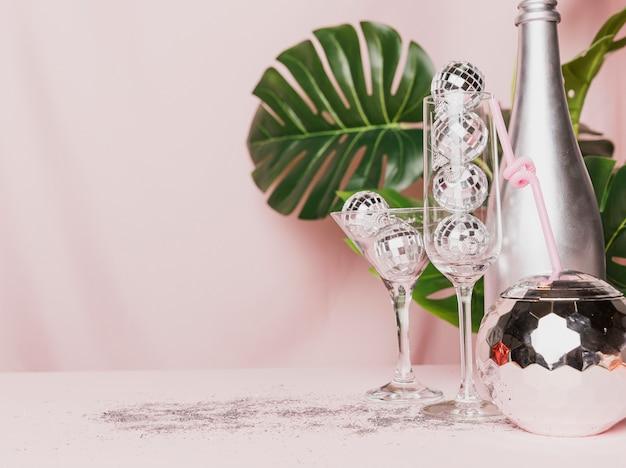 Vista frontal de copas de champán transparentes con bolas de discoteca