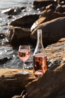 Vista frontal copas de vino y botella en las rocas del océano