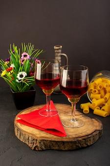 Una vista frontal copas de vino en un escritorio de madera marrón junto con flores y pasta italiana cruda en un escritorio oscuro