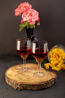 Una vista frontal copas de vino en un escritorio de madera marrón junto con flores y pasta italiana cruda en la oscuridad.