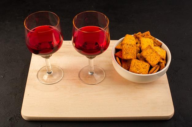 Una vista frontal de copas de vino junto con patatas fritas dentro de la placa en un escritorio de madera y oscuro