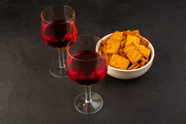Una vista frontal de copas de vino junto con patatas fritas dentro de la placa en la oscuridad
