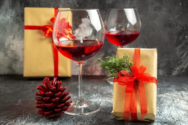 Vista frontal copas de vino regalos de navidad en la oscuridad