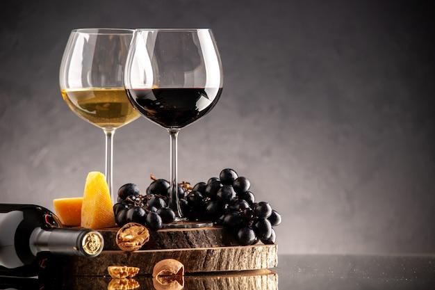 Vista frontal copas de vino uvas frescas nueces queso amarillo sobre tablero de madera botella volcada sobre fondo oscuro