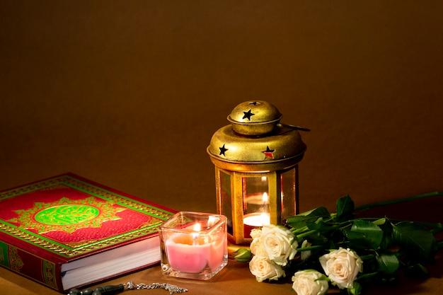 Vista frontal del corán con velas y rosas.