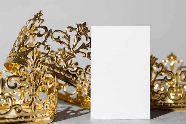Vista frontal de las coronas de oro del día de la epifanía con tarjeta en blanco