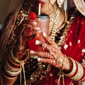 Vista frontal de la cosecha de la novia india es drinkinkg cocktail en vestimenta tradicional