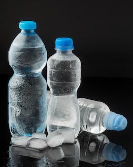 Vista frontal de cubitos de hielo y botellas de agua