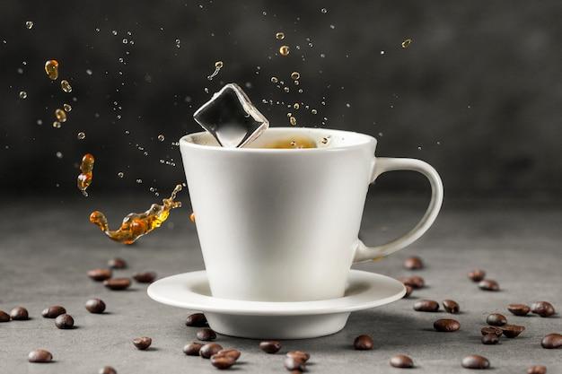 Vista frontal del cubo de hielo chapoteando en la taza de café