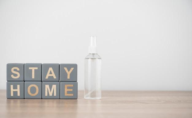 Vista frontal de cubos de madera con stay home y desinfectante de manos