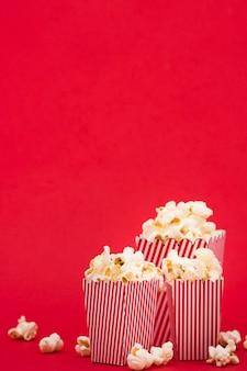 Vista frontal cubos de palomitas de maíz sobre fondo rojo.