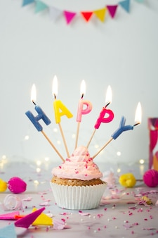 Vista frontal de cupcake de cumpleaños con velas encendidas