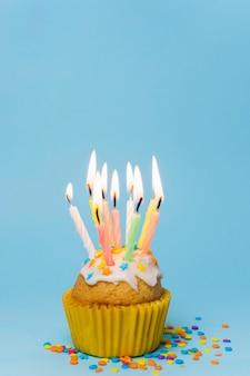 Vista frontal cupcake con velas encendidas y espacio de copia