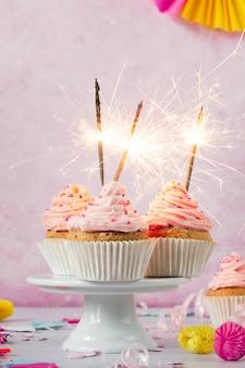 Vista frontal de cupcakes de cumpleaños con glaseado y bengalas