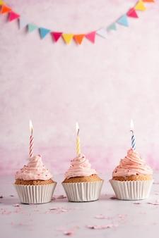 Vista frontal de cupcakes de cumpleaños con guirnaldas y velas encendidas