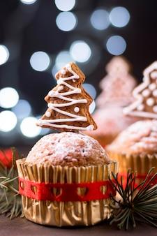 Vista frontal de cupcakes navideños con cobertura de árbol de pan de jengibre