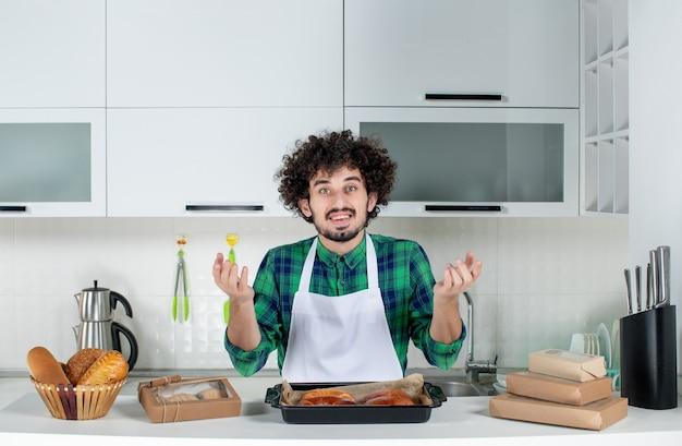 Vista frontal del curioso hombre de pie detrás de la mesa con pasteles recién horneados en la cocina blanca