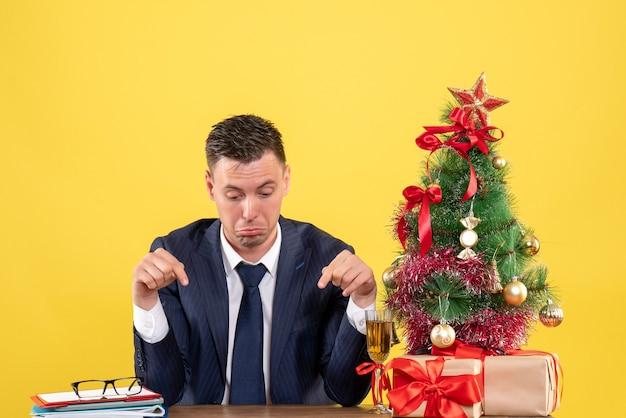 Vista frontal del dedo del hombre deprimido apuntando a la mesa sentado en la mesa cerca del árbol de navidad y regalos en amarillo