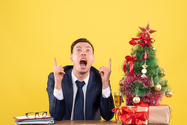 Vista frontal del dedo del hombre emocionado apuntando hacia arriba sentado en la mesa cerca del árbol de navidad y presenta en amarillo