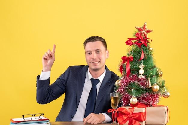 Vista frontal del dedo del hombre feliz apuntando hacia arriba sentado en la mesa cerca del árbol de navidad y regalos en amarillo