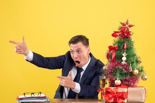 Vista frontal del dedo del hombre feliz señalando algo sentado en la mesa cerca del árbol de navidad y presenta en amarillo