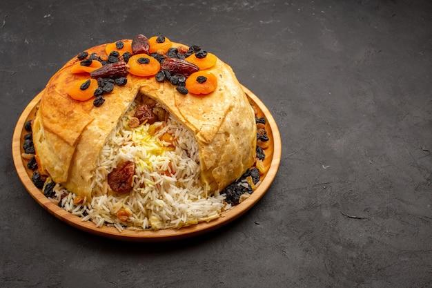 Vista frontal de la deliciosa comida de arroz shakh plov cocinada dentro de masa redonda con pasas en el espacio gris
