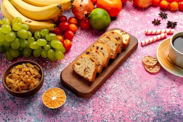 Vista frontal deliciosa composición de frutas con tortas en rodajas y té en el escritorio rosa