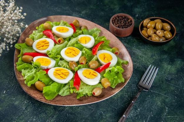 Vista frontal deliciosa ensalada de huevo se compone de aceitunas y ensalada verde sobre fondo oscuro