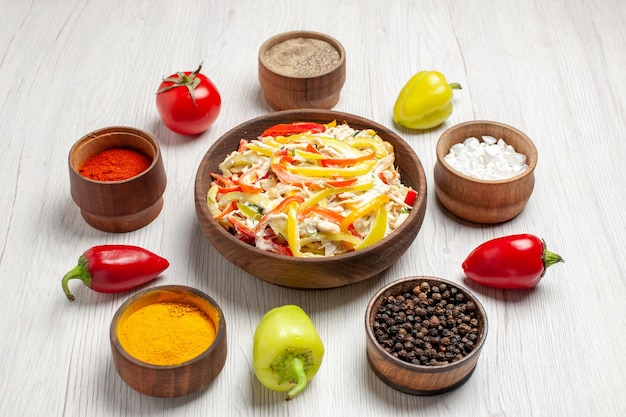 Vista frontal deliciosa ensalada de pollo con diferentes condimentos en un escritorio blanco bocadillo comida madura carne fresca
