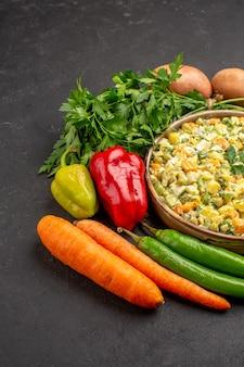 Vista frontal de una deliciosa ensalada con verduras frescas en superficie oscura